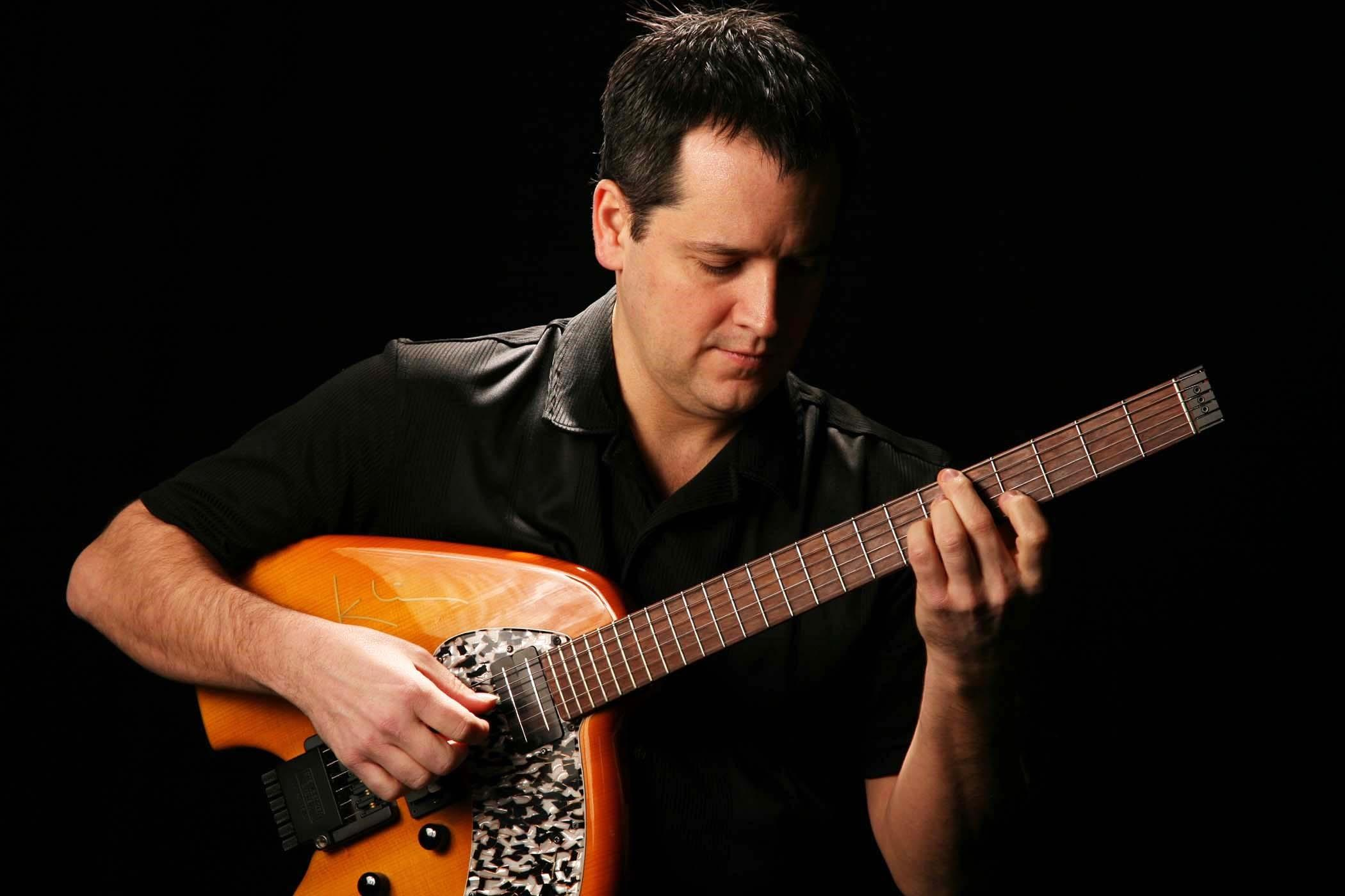 Musician Tom Lagana romancing his guitar.