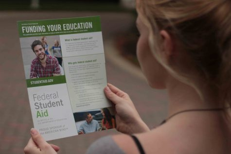 An AACC student reads the Federal Student Aid handbook to learn about the new FAFSA deadline.