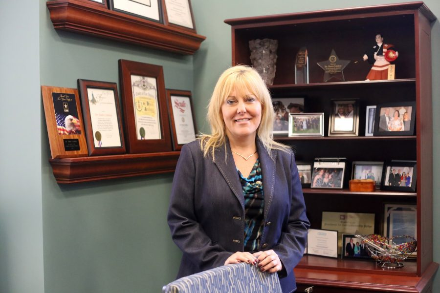 President Dawn Lindsay stands before her many awards, accolades, and mementos.