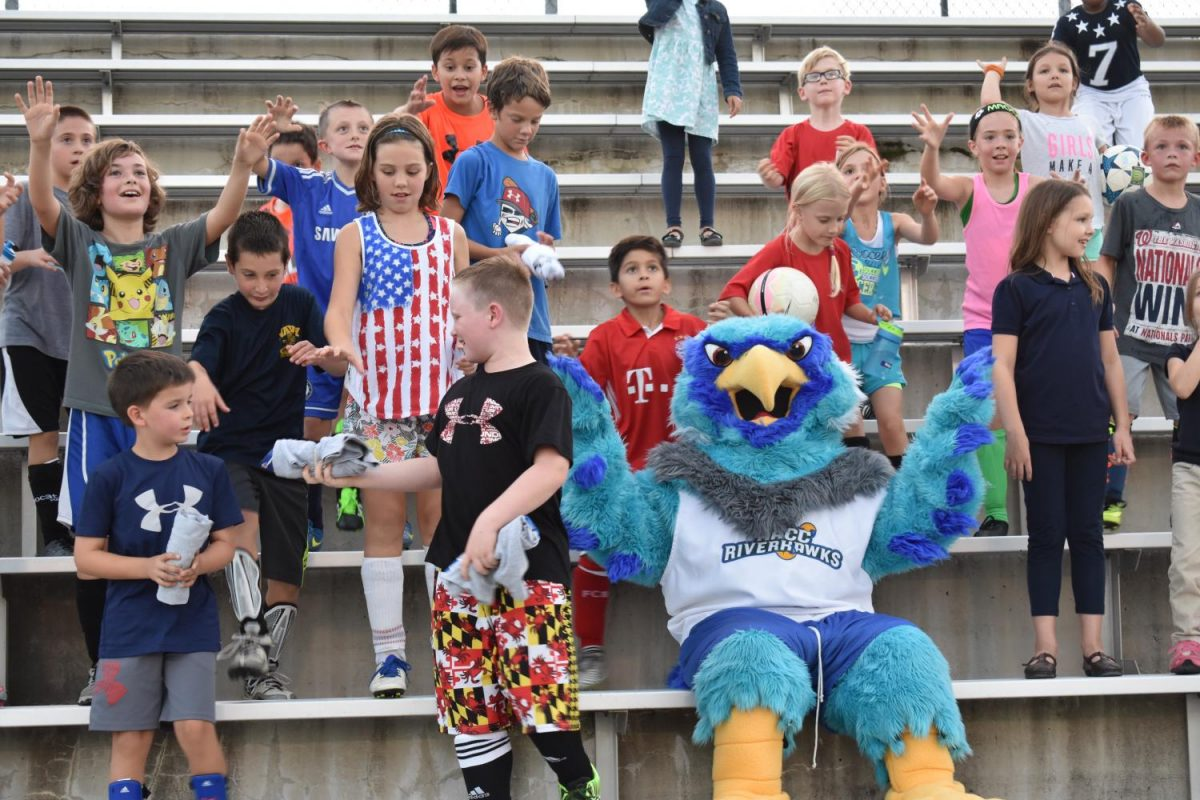 AACC mascot Swoop poses with kids from the community outreach event.