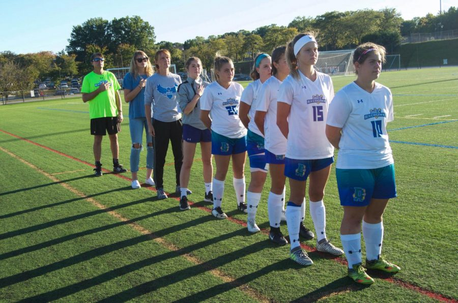 Women's Soccer teammates stand with their coach for the national anthem before a game.