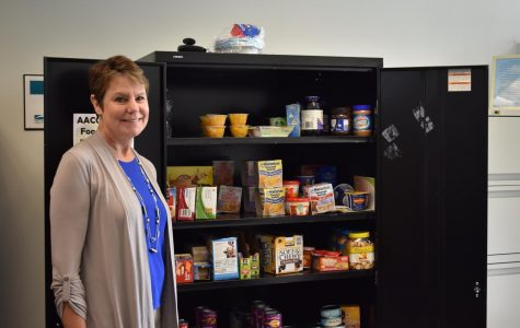 Director of Student Engagement Chris Storck stands beside the food pantry in her office; the pantry offers food to students who can't afford meals.