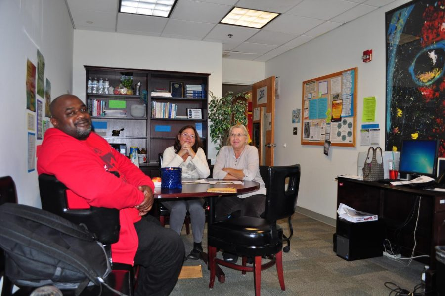 Ron Easley (left) and Gwinn Spence work under Loretta Lawson-Munsey at the lounge-like recovery center to help other students escape drug addictions.