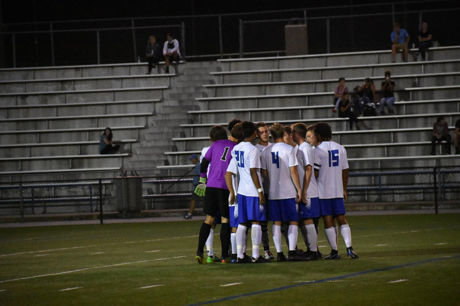 Men's Soccer players huddle before a game. Photo by Sarah Alonso