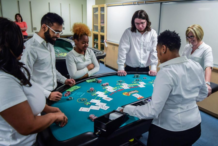 Mohammad Zaidi (left), Taylor Williams (center-left), Joseph Williams-Overton (center-right) and Tanjanigua Swindell practice running games with each other in the Act 1 Blackjack Dealer class, Games 300.