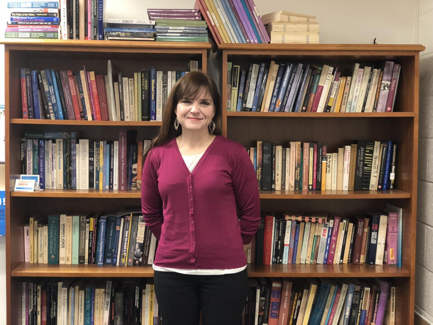 Dr. Heather Rellihan poses in front of a gender studies-themed bookcase outside of her office.