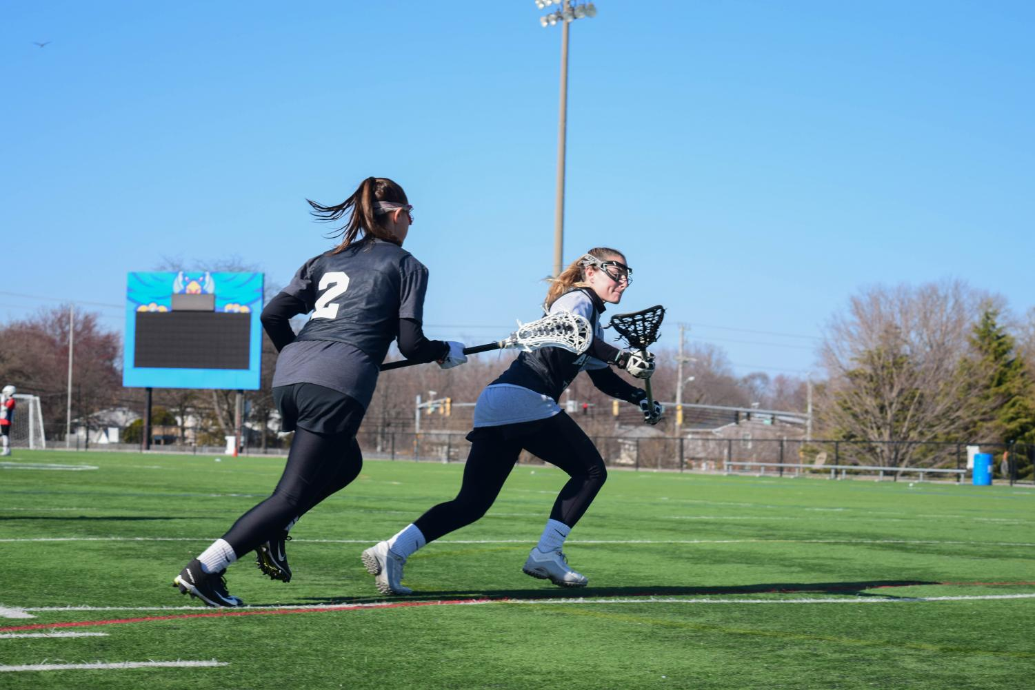Lacrosse players Payton Baronella-O'Toole and MacKenzie Schwartz practice for a game. Some athletes will be able to count developmental courses in their GPAs next fall.