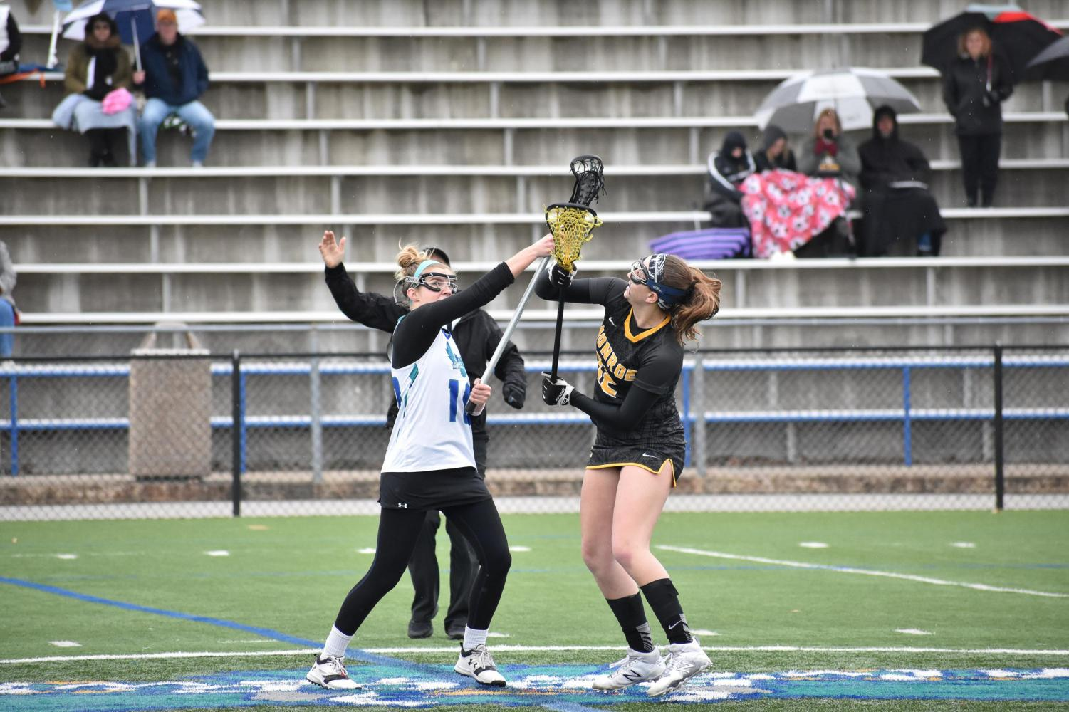 Defender Kara Steir (left), attack Caitlyn Shriver and goalie Deanna Valerien (right) prevent a Monroe player from scoring.