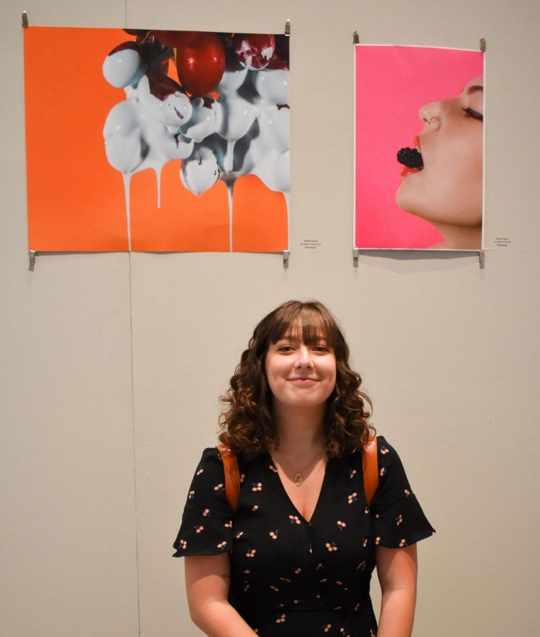 Hannah Tenner kneels in front of her photographs,