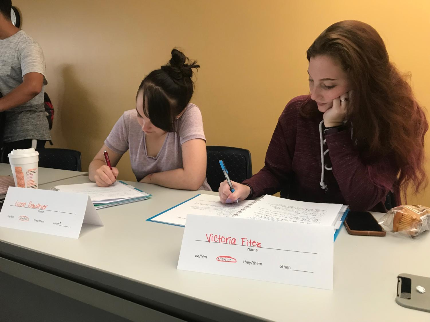 First-year students Lizzie Gauthier and Victoria Fitez take notes in Dr. Rachelle Tannenbaum's psychology class. Tannenbaum uses name cards during her classes to display students' preferred pronouns.