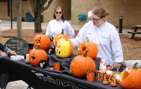 Club adviser Carrie Svoboda and second-year culinary student Emily Parent arrange pumpkins at today's culinary event.
