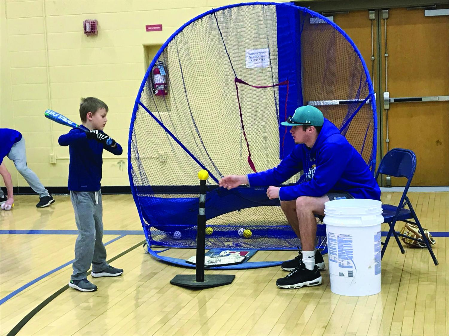 AACC Baseball player John Shupe teaches a youth player how to hit off of a tee.