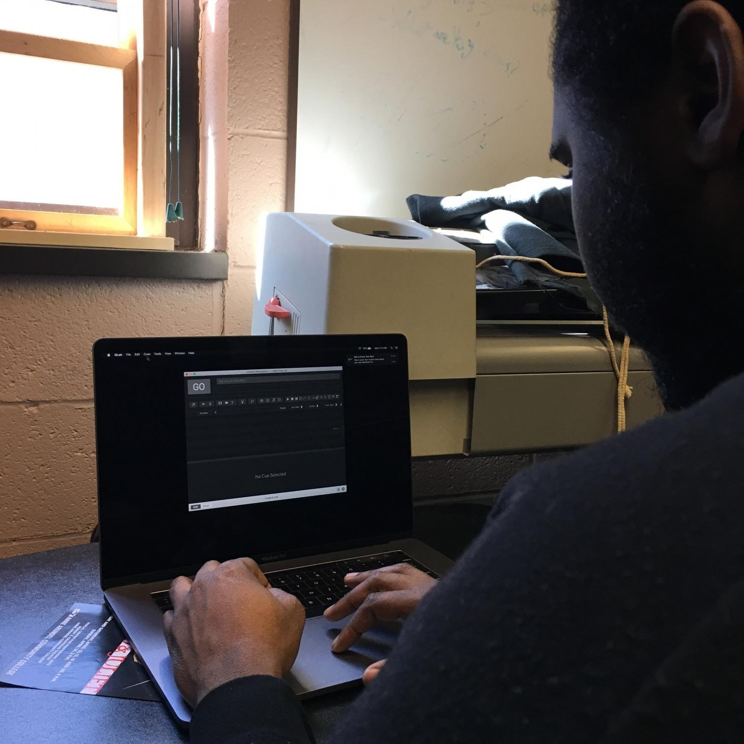 Shawn Smith, a returning game development student, using computer design to help production for Romeo and Juliet.