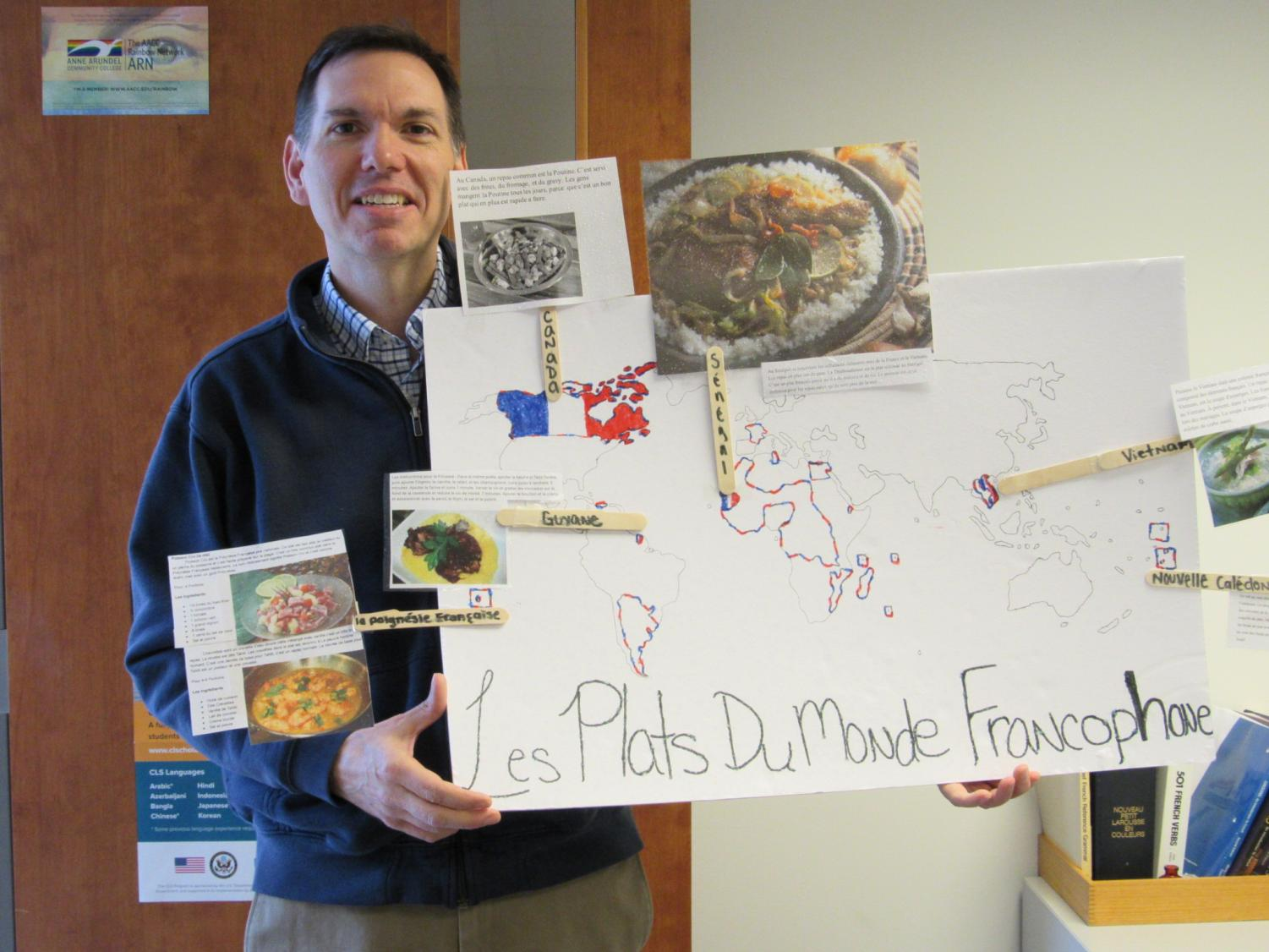 Professor Scott Cooper, World Languages Dept Chair, displays a French poster.