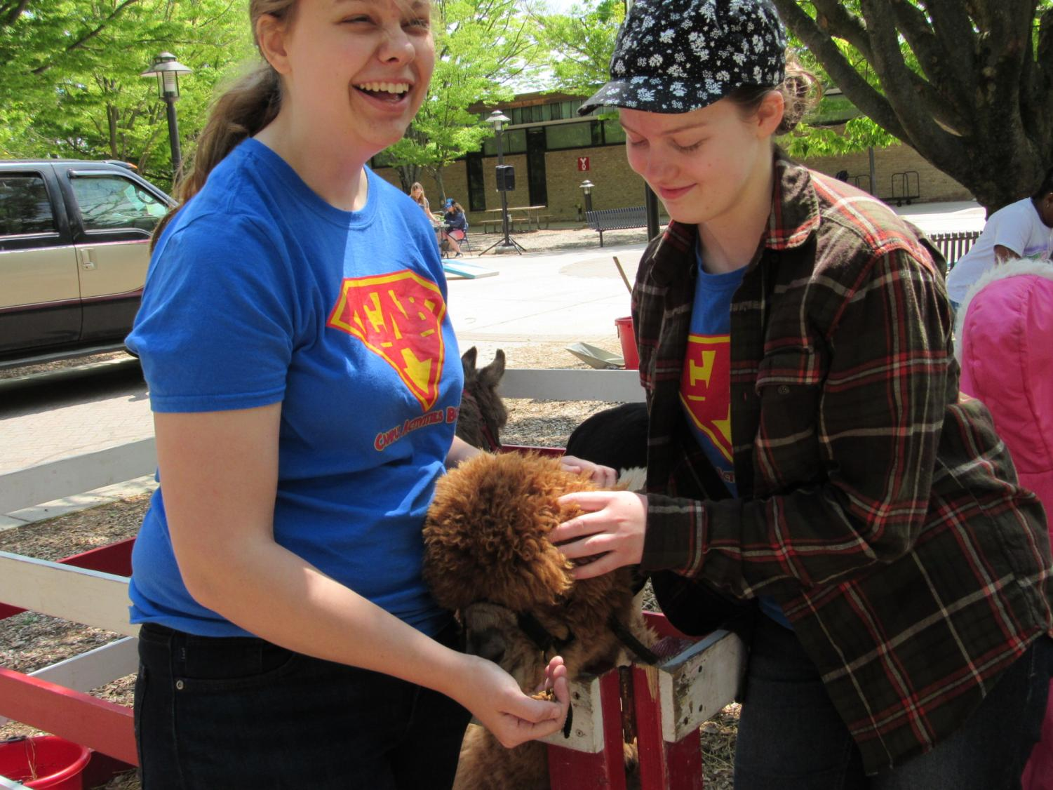 CAB executive board members Kristin Kohout and Catrina Murphy feed an alpaca at the Earth day petting zoo.