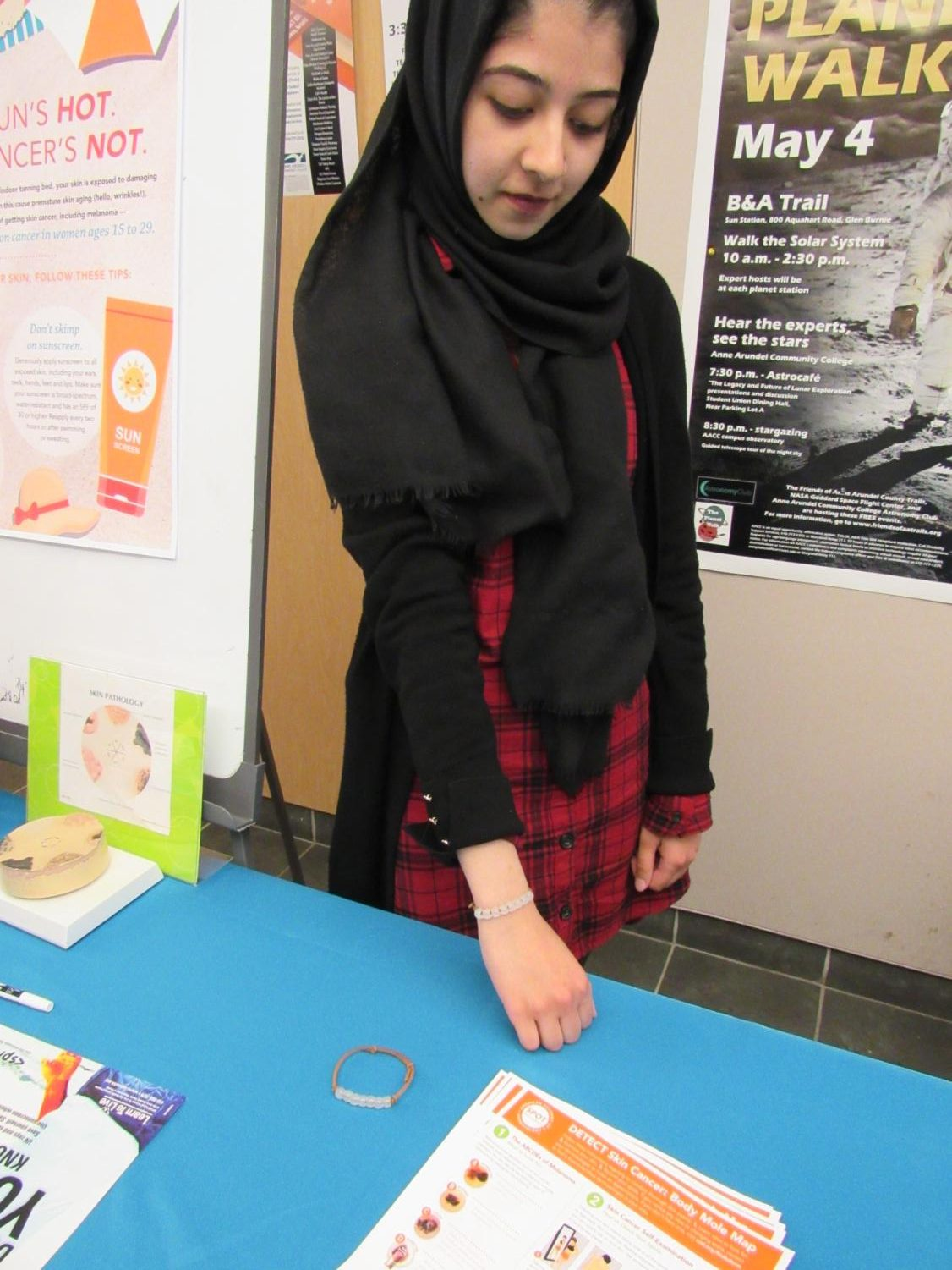 Lahiba Ijaz, a first-year business administration student, demonstrates how to use a special UV bracelet.