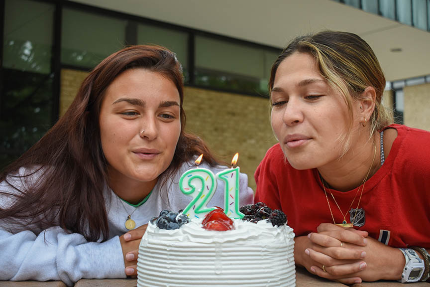 First-year nursing students Allie Riecke (left) and Kara Kishis blow out birthday candles on the Quad.