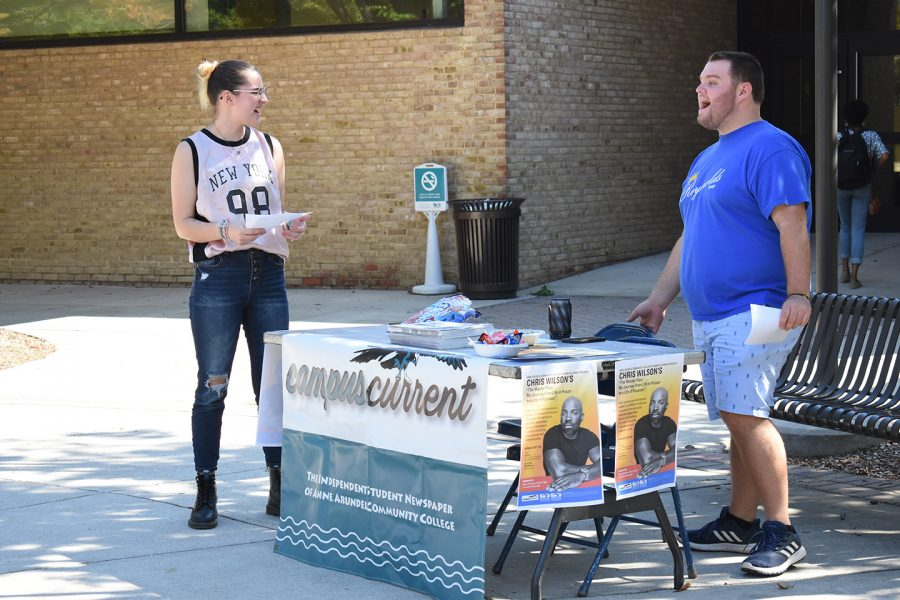 Ren Bishop, a third-year psychology student (left) and Jake Brannon, a second-year transfer studies student advertise the upcoming speech by author Chris Wilson on the quad.