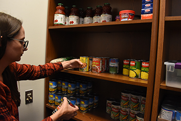 A specialist who spoke at AACC says poverty affects students' grades and experience. Pictured: A student worker selects items from the campus food pantry.