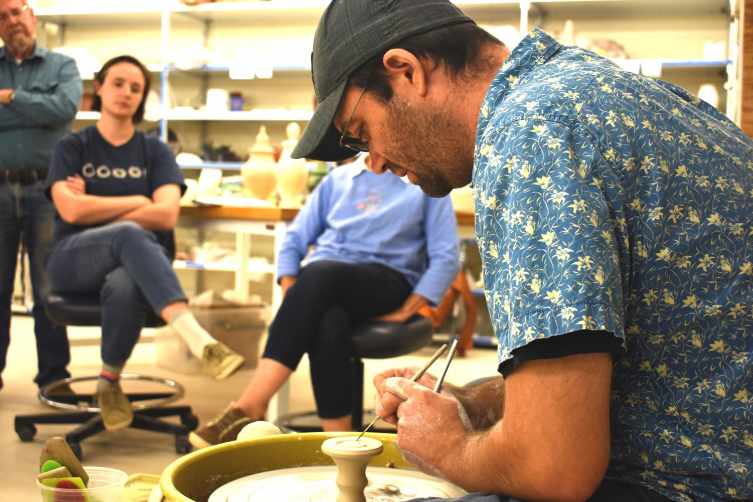 Jason Piccoli gives a demonstration of his technique on a pottery wheel to the students of AACC