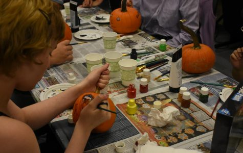 Students paint pumpkins with members from the Entrepreneurs Club.
