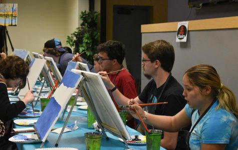 Students paint along with an instructor, creating a fall landscape.