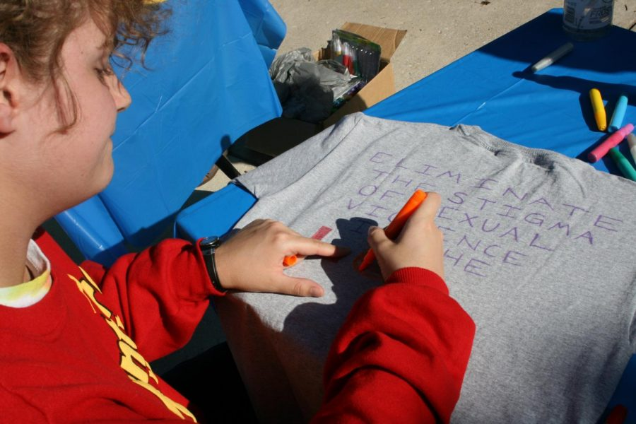 A student draws a t-shirt campaigning against the stigma of sexual assault survivors.