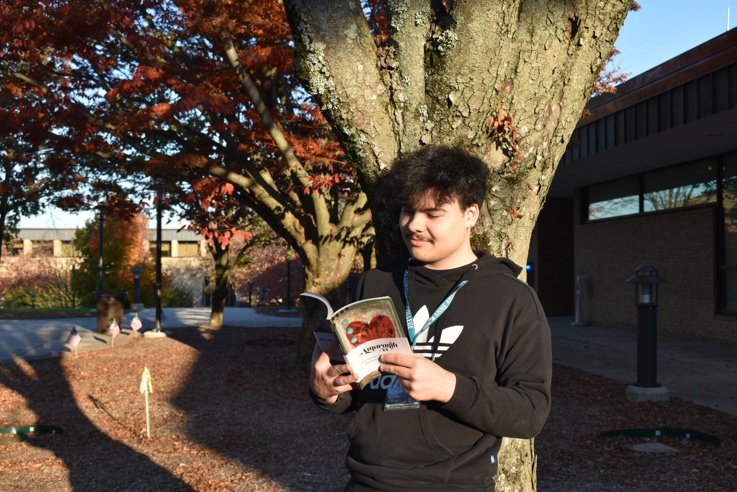 Amaranth Editor-in-Chief Mitchell Santos reads the issue of the literary magazine that won the Pacemaker Award this November.