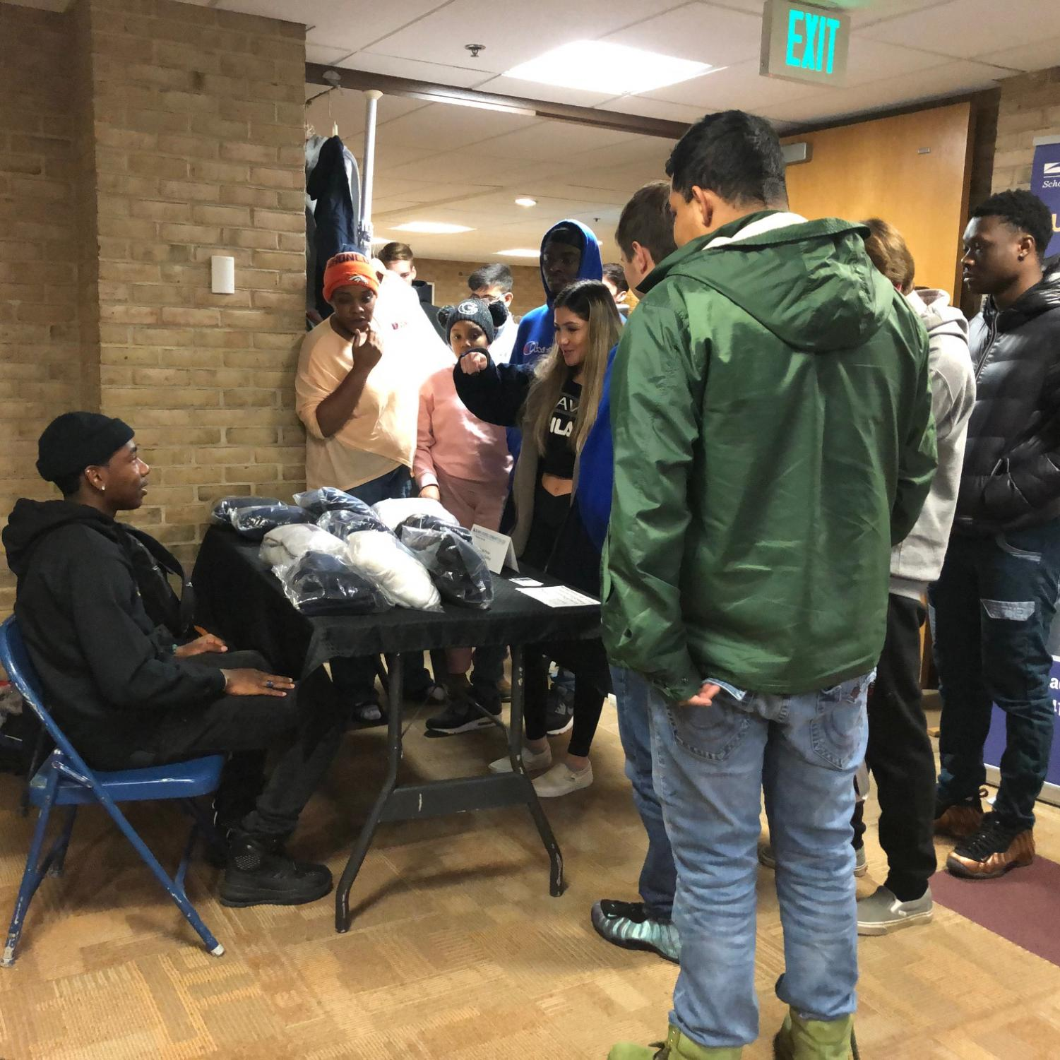 Students surround first-year business management and marketing student Josiah Parker, who sells his merchandise at a table during the Best of Business Trade Show.
