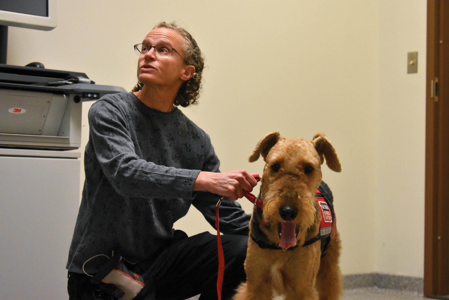 English Professor Jessica Rabin helps her service dog, Caleb, through his airport security training.