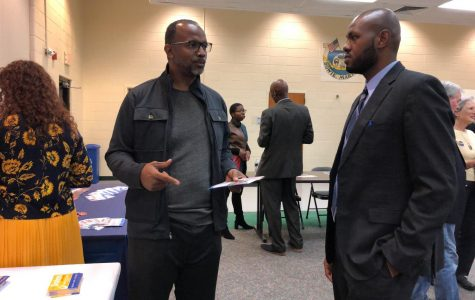 A voter, left, speaks with Darian-Senn-Carter, a professor in AACC's Homeland Security and Criminal Justice Institute who is running for a seat on the Bowie City Council.