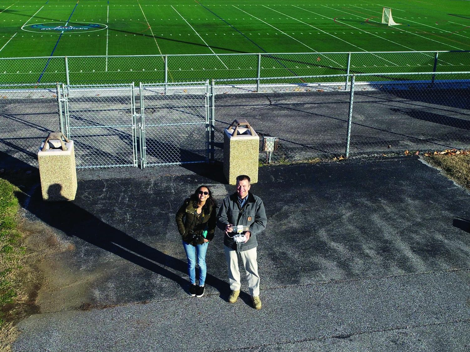 Former Campus Current Editor-in-Chief Amber Nathan watches Tim Tumelty, who is in charge of AACC's drone program, fly a drone on campus.