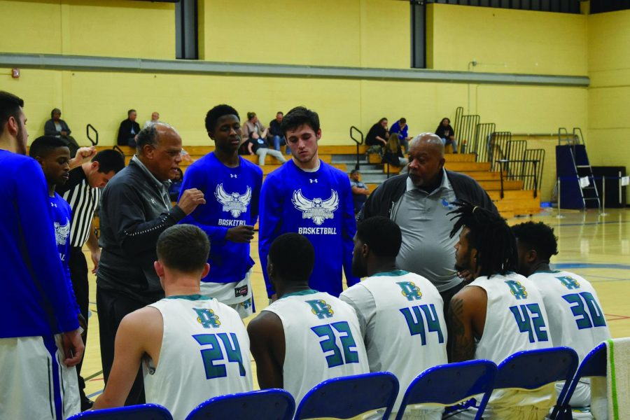 Men's Basketball coach Joe Snowden (left) speaking during a timeout to forward Michael Sullivan, guard Matthew Kern and assistant coach Joe Gray.