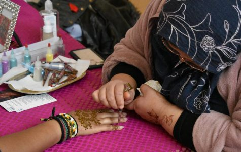 Henna artists puts designs on student hand's