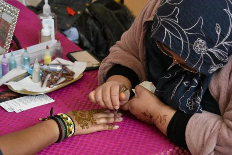 Henna artist Marcela Faruqui applies the design to a student's hand.