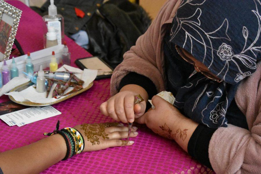 Henna+artist+Marcela+Faruqui+applies+the+design+to+a+student%27s+hand.+
