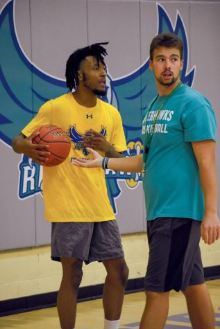Campus Current reporters regularly interview coaches and players for Men's Basketball forward Keith Wyatt Jr. (left) works with assistant coach Clinton Smith.