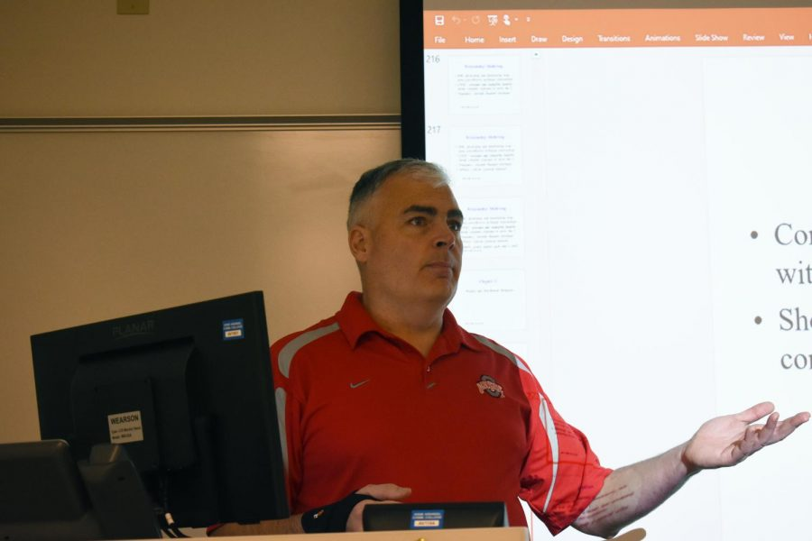 Adjunct business instructor Lou Carloni teaches in front of a projector.