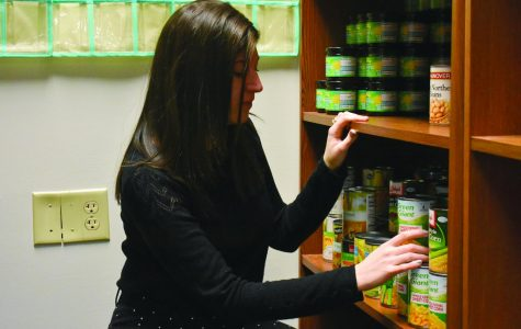 Basic needs coordinator Catlin Silver reaches into the food pantry.