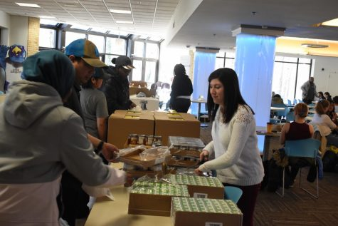 Basic needs coordinator Caitlin Silver handing out canned food to students at the Heart Market.