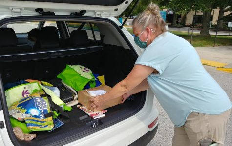 Health and Fitness Assistant Mary Moorer loads a curbside order from the AACC Bookstore in the back of a student's car.