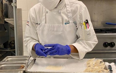 Culinary student Jeanette Pesseh wears a mask and gloves as she cooks for a class on campus.