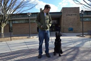 Service animal experts encourage students to volunteer to raise service animals for veterans. Shown, former journalism student Michael Garvey, a veteran, and his service dog Liberty, on campus in 2017.