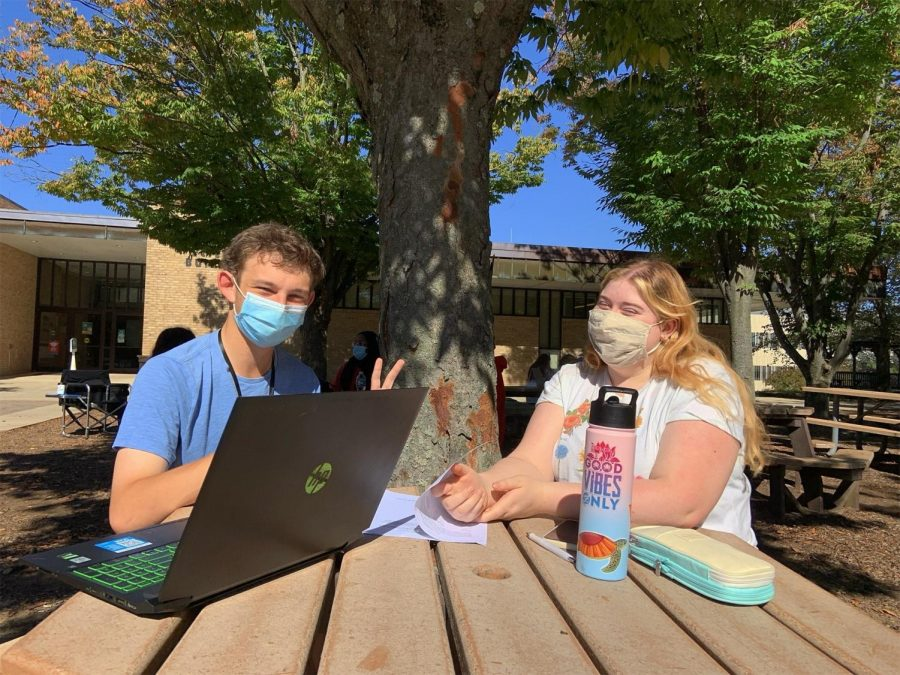 First-year transfer studies students Arnold Beck and Kestrel Watson mask up before meeting on the Quad.